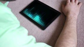 Una lista de temas genérica que juega en un dispositivo negro de la tableta - versión azul del inconformista del indie almacen de metraje de vídeo