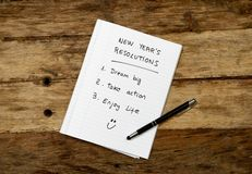 Una lista di 2019 risoluzioni del nuovo anno redatta sul taccuino e sul fronte felice sulla tavola di legno nei migliori scopi di immagini stock