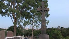 Una llamada y las cigarras del ` s del cuervo son los sonidos del fondo en el cementerio con la vista distante de la ciudad de Br metrajes