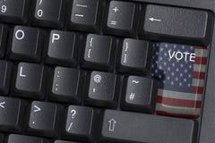 Una llave señalada por medio de una bandera americana del VOTO en un teclado de ordenador Imagen de archivo libre de regalías
