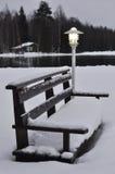 Una lámpara y un banco cubiertos con nieve Imagenes de archivo