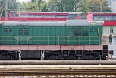Una locomotiva di verde del ferro sta ad una stazione ferroviaria immagine stock