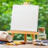 Una lona en blanco en el caballete, las brochas artísticas y los tubos de la pintura Fotografía de archivo libre de regalías