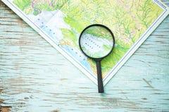 Una lupa en el fondo del mapa Imagen de archivo libre de regalías