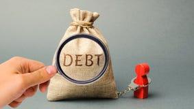 Una lupa está mirando un bolso del dinero con la deuda de la palabra y un prestatario es limitado por las esposas Pago obligatori foto de archivo libre de regalías