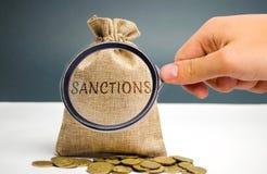 Una lupa está mirando un bolso del dinero con las sanciones de la palabra La imposición de sanciones económicas/políticas en imagen de archivo