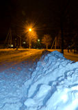 Una luz de antorchas inunda un camino encuadernado de la nieve nocturna en el outskir Fotos de archivo
