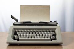 Una máquina de escribir retra blanca con la hoja amarilla Imagen de archivo libre de regalías