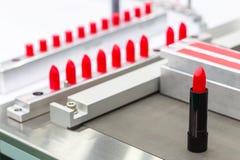Una máquina de rellenar del frasco del lápiz labial en una fábrica de los cosméticos foto de archivo
