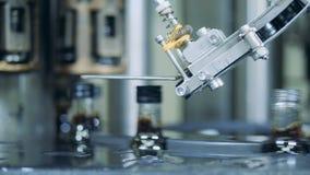 Una máquina pone los casquillos en las botellas con el alcohol en un transportador, cierre para arriba almacen de metraje de vídeo