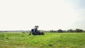 Una máquina segador azul siega la hierba en el campo almacen de metraje de vídeo