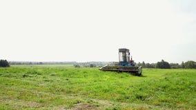 Una máquina segador azul siega la hierba en el campo El tractor siega la hierba metrajes