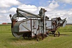 Una máquina trilladoa vieja reside en un campo con un tren de carga que pasa en el fondo Imagen de archivo libre de regalías