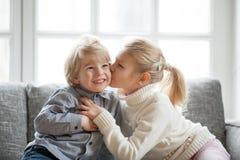 Una más vieja hermana del niño que abraza besando al pequeño hermano menor en h Foto de archivo libre de regalías
