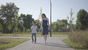 Una más vieja hermana que camina con el hermano menor que lleva a cabo las manos en el parque del verano El muchacho travieso cor metrajes