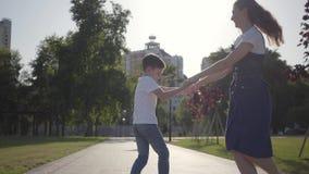 Una más vieja hermana que hace girar alrededor con el hermano menor que lleva a cabo las manos en el parque del verano Ocio al ai metrajes