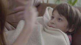 Una más vieja hermana que juega con poco cierre del hermano para arriba El muchacho que miente en la cama cubierta con una manta, almacen de metraje de vídeo