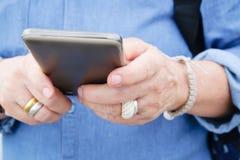 Una más vieja mujer con el teléfono elegante Foto de archivo libre de regalías