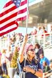 Una más vieja mujer con la bandera y camiseta para mujer de marzo en la reunión política con la muchedumbre borrosa detrás de ell imágenes de archivo libres de regalías