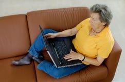 Una más vieja mujer con la computadora portátil imagenes de archivo