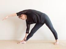 Una más vieja mujer en actitud lateral de la yoga Fotos de archivo