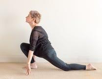 Una más vieja mujer en la posición de la estocada de la yoga Imagen de archivo