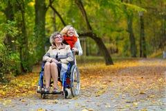 Una más vieja mujer en la silla de ruedas con la mujer joven en el parque Fotos de archivo libres de regalías