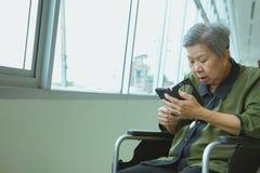 una más vieja mujer en la silla de ruedas que sostiene el teléfono móvil sorprendido chocado fotos de archivo