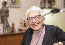 Una más vieja mujer independiente que se sienta en el parque feliz y la sonrisa Imagen de archivo