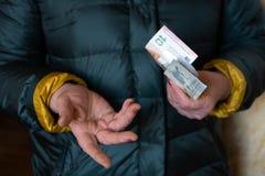 Una más vieja mujer mayor sostiene los billetes de banco EURO - del este - pensión europea del sueldo fotos de archivo libres de regalías