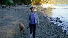 Una más vieja mujer que camina en la playa con su perro almacen de video