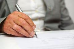 Una más vieja mujer que firma el documento foto de archivo libre de regalías