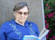 Una más vieja mujer que lee un libro en su jardín Foto de archivo