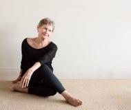 Una más vieja mujer que sonríe haciendo yoga Imagen de archivo libre de regalías
