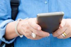 Una más vieja mujer que usa el teléfono elegante Imágenes de archivo libres de regalías
