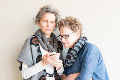 Una más viejas madre e hija con el teléfono elegante Imágenes de archivo libres de regalías