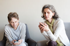 Una más viejas madre e hija que usa smartphones Fotografía de archivo libre de regalías