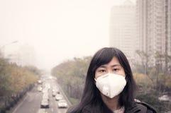 Una máscara de la boca de la muchacha que lleva contra la contaminación atmosférica Foto de archivo libre de regalías