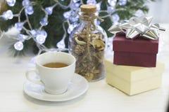 Una mañana brillante festiva con una taza de botella del té, de cristal con las flores secas y de giftboxes Fotos de archivo libres de regalías