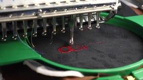 Una macchina automatizzata ricama il modello con i fili rossi su un panno nero Attivit? di robotica nell'adattamento della linea  archivi video