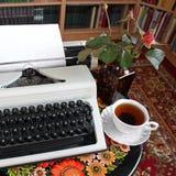 Una macchina da scrivere, tè e una rosa in un vaso immagini stock libere da diritti