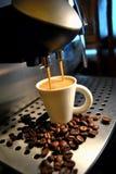 Una macchina del caffè e una tazza bianca Fotografie Stock