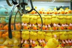 Una macchina dell'artiglio è riempita di giocattoli gialli della peluche fotografia stock