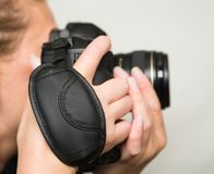 Una macchina fotografica della foto con una cinghia del polso in belle mani femminili fotografia stock libera da diritti