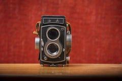 Una macchina fotografica reflex della lente del gemello del gabbiano 4 TLR con la cinghia marrone su un fondo rosso, Nottingham,  immagini stock libere da diritti