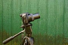 Una macchina fotografica sui precedenti di una parete di legno verde della casa Immagine Stock Libera da Diritti