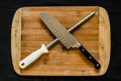 Una macchina per affilare i coltelli, o smerigliatrice acciaio e un coltello del cuoco unico su un tagliere fotografia stock libera da diritti