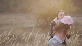 Una madre alegre gira a su pequeña hija, risas y la abraza en el medio de la estepa almacen de metraje de vídeo
