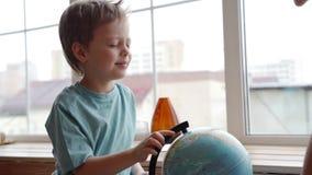 Una madre atractiva de la pertenencia étnica caucásica utiliza un globo para mostrar a su hijo joven los países del mundo almacen de metraje de vídeo