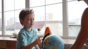 Una madre atractiva de la pertenencia étnica caucásica utiliza un globo para mostrar a su hijo joven los países del mundo almacen de video